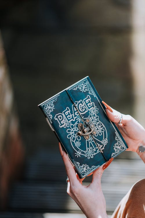 Crop anonymous female with vintage magic diary in manicured hands on blurred background in daytime