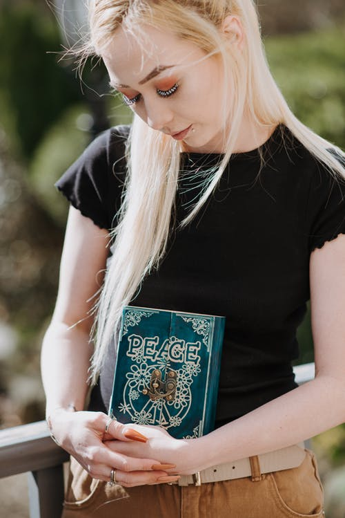 Young soothsayer embracing magic book in terrace