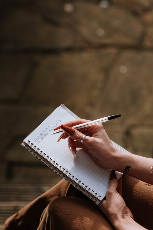 Woman with long manicure taking notes in copybook