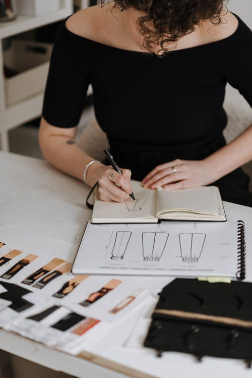 Anonymous female designer drawing sketch of new clothes while sitting at table with samples of fabrics during work in studio