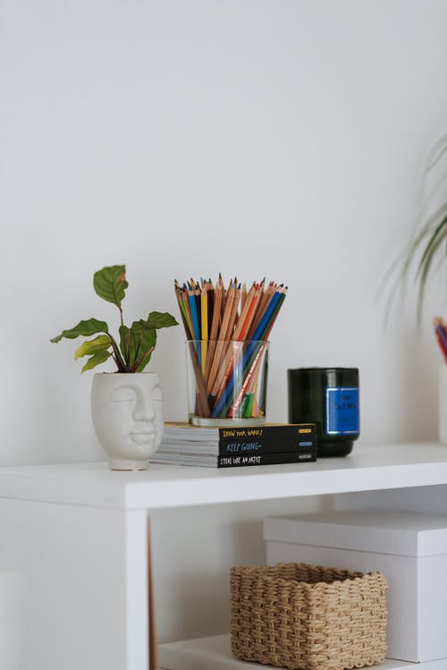 Green potted plant placed on white table with set of multicolored pencils for drawing on books at wall in room with wicker basket