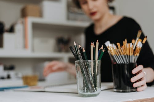 Crop woman at table with art supplies