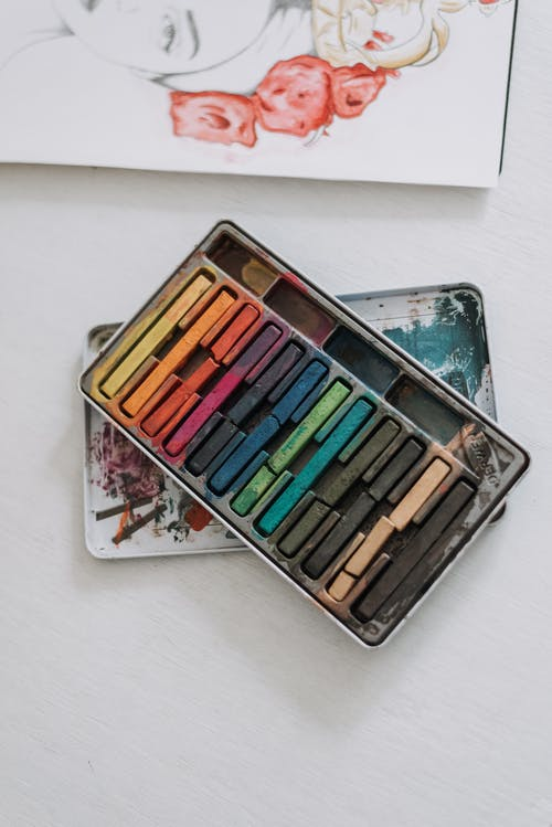 Top view of assorted colorful crayons for drawing placed on white background with painted picture in modern light art studio