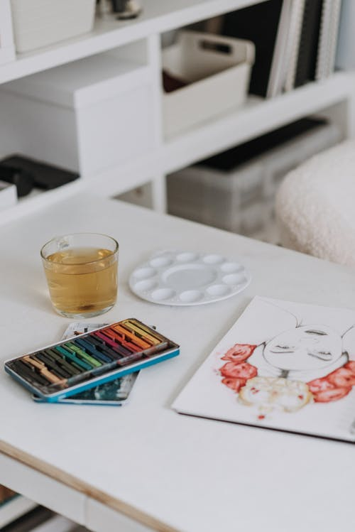 Set of colored crayons near glass with water placed on table with creative drawing and palette in modern light art studio