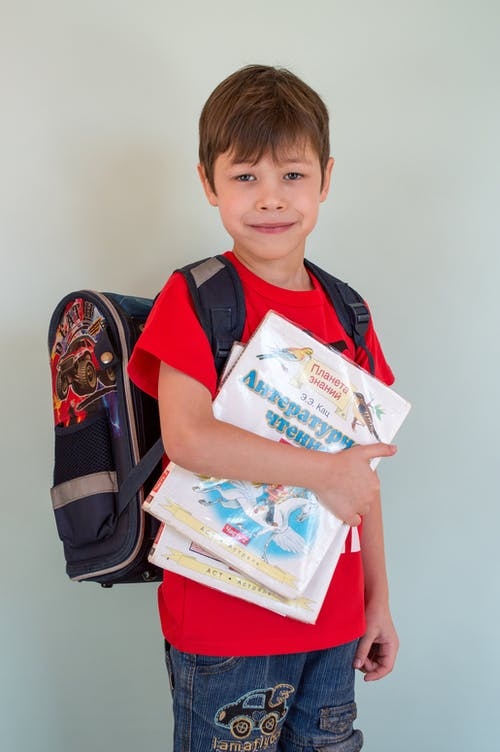 Little boy with backpack and textbooks