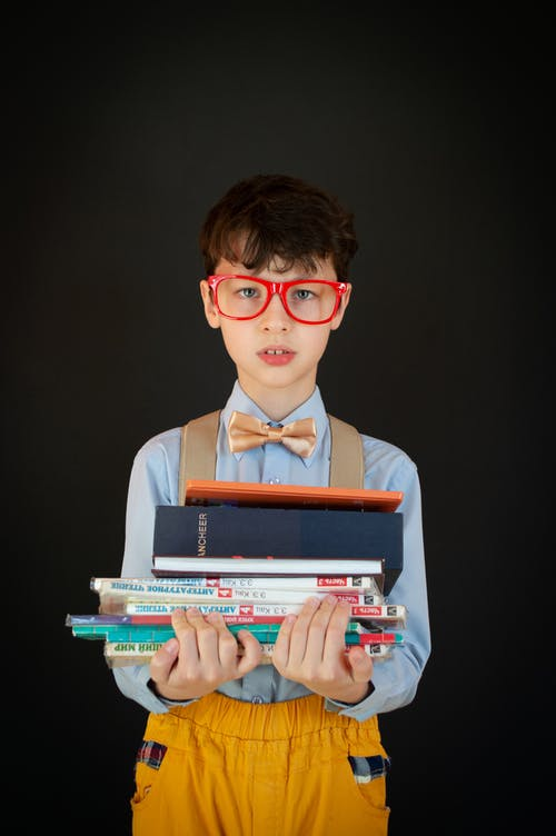 Smart schoolboy with stack of books