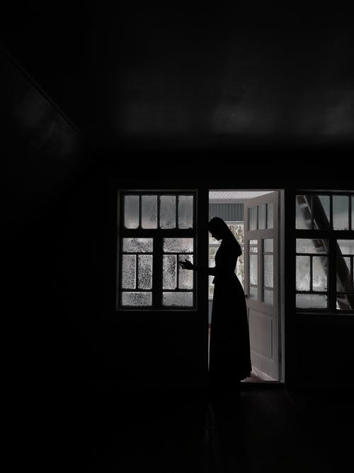 Side view of silhouette of anonymous female in dress standing in doorway in house in daytime