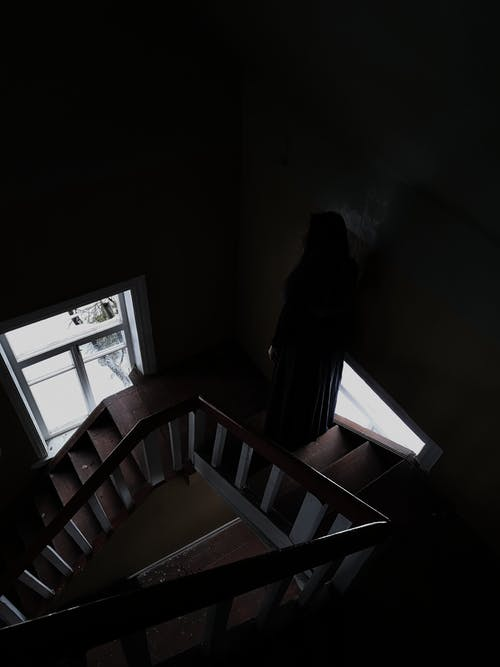 Faceless person on stairs in dark building with windows