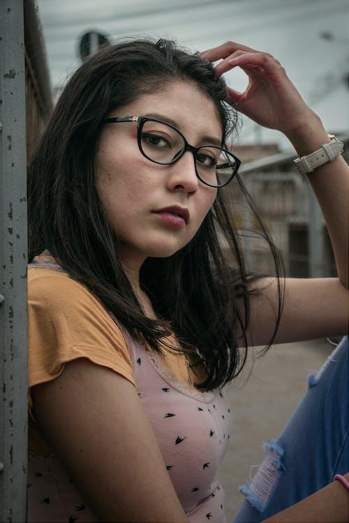 Woman in Orange T-shirt Wearing Black Framed Eyeglasses