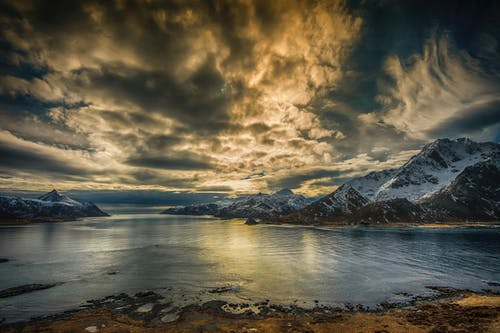 Snow Covered Mountain Near Body of Water Under Cloudy Sky