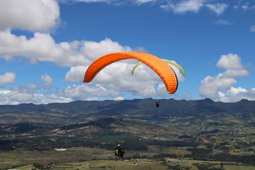 Person Paragliding with Orange Parachute