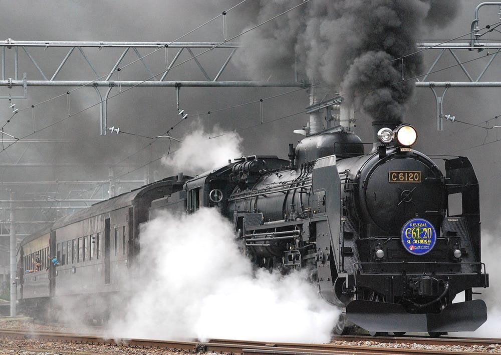 A train on rail and showing smoke.   Photo: Pexels