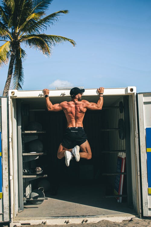 Man in Black Shorts Sitting on White Truck