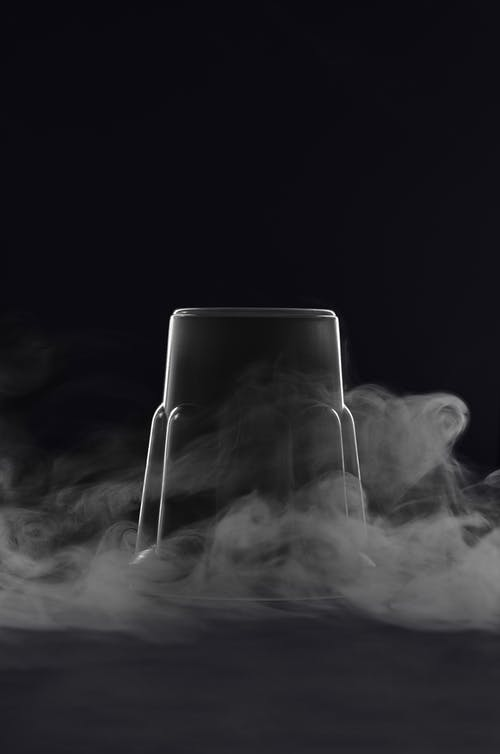Transparent inverted glass cup with cloud of steam against black background in studio