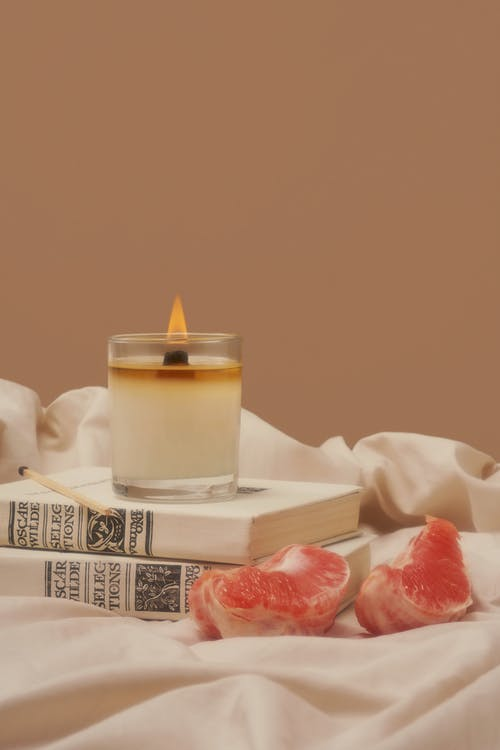 Flaming wax candle placed on books near pieces of grapefruit on creased fabric against beige background