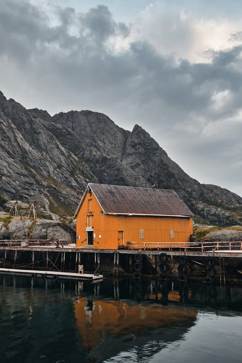 Brown Wooden House on Dock Near Mountain