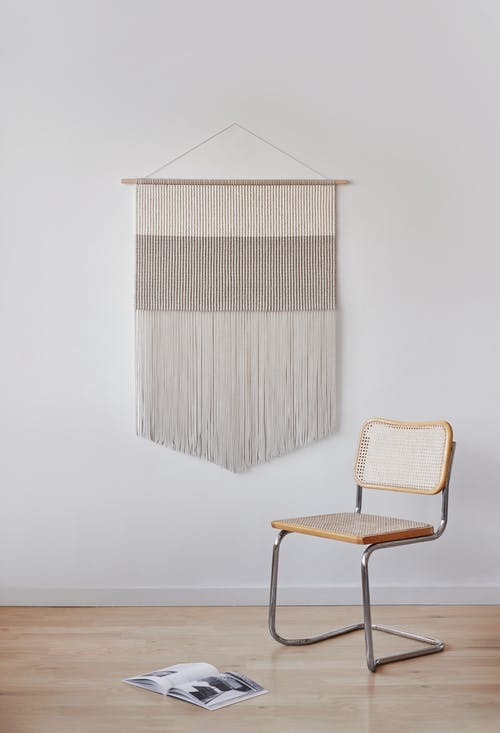Decorative element hanging on wall in room with minimalist design