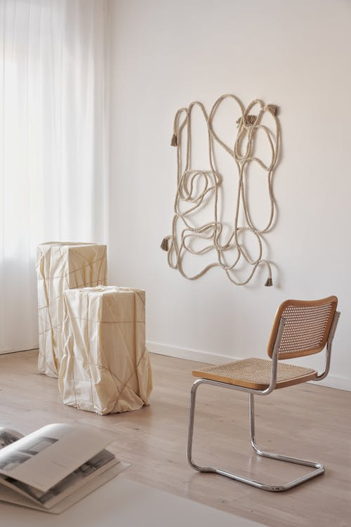 Interior of room with rope decor hanging on wall in room with chair placed near pedestal and opened magazine on table