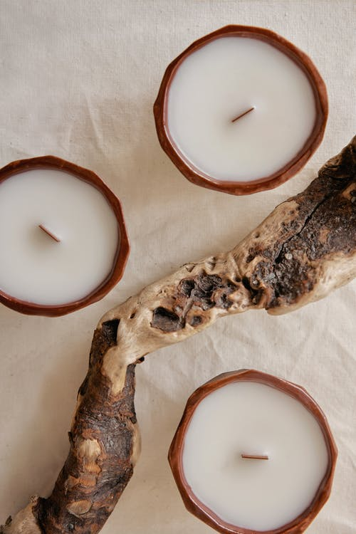 Decorative aroma candles near driftwood on creased fabric