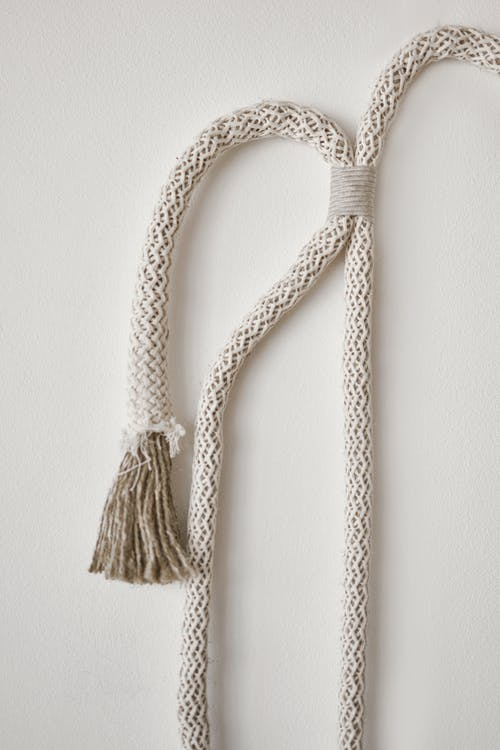Texture of curved tied rope for minimalist decor hanging on white wall in light room
