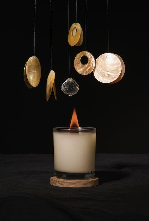 Burning aroma candle placed under round shaped hanging decor against dark black background