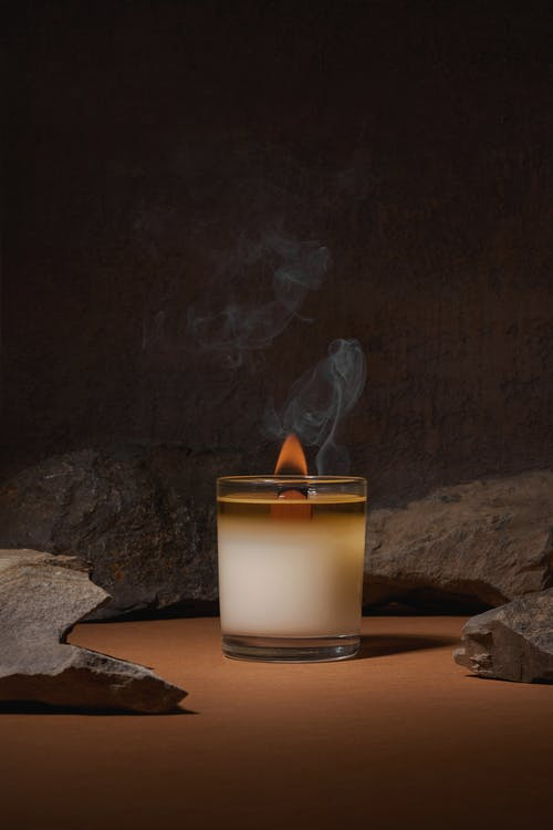 Burning fuming candle placed near boulders