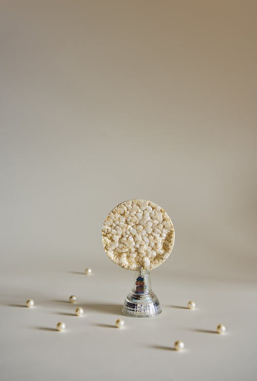 Composition of puffed rice cake on metallic stand around small pearls in white studio