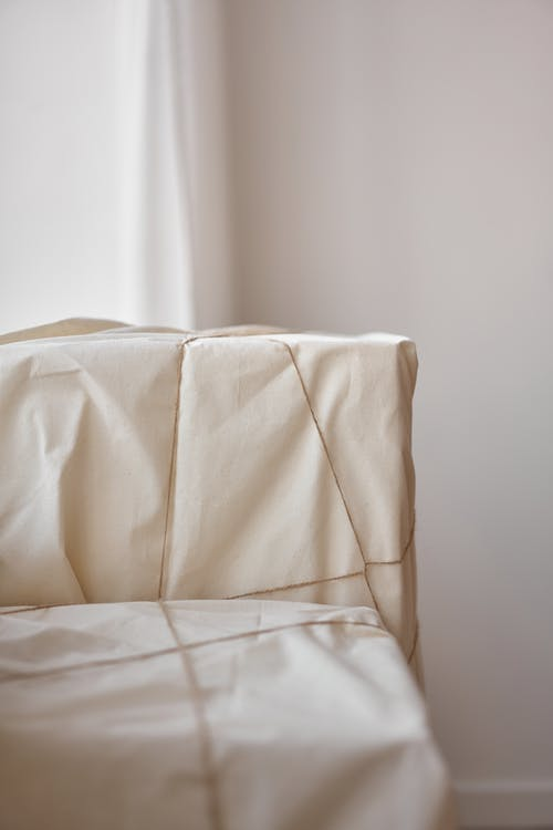 Big boxes wrapped in white cloth and tied with rope placed near white wall and curtain
