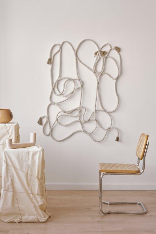 Minimalist decor with pedestals under cloth near chair