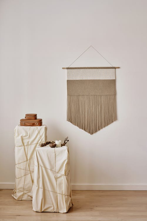 Decor hanging on white wall near pedestals with candles and bags as art installation