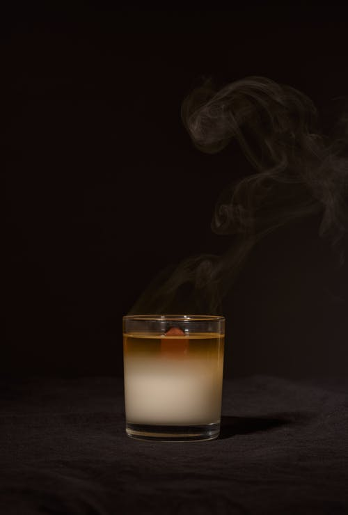 Wax aroma candle in transparent glass holder with smoke placed against black background