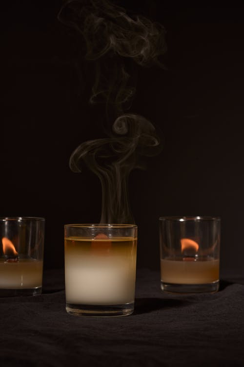 Burning aroma candles in glass holders emitting smoke placed against black background in studio