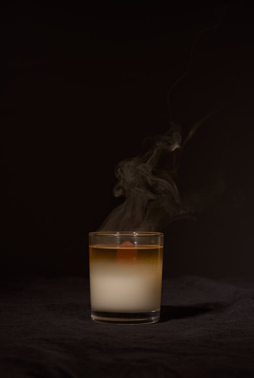 Transparent glass holder with aromatic candle with fume for relaxation against dark black background