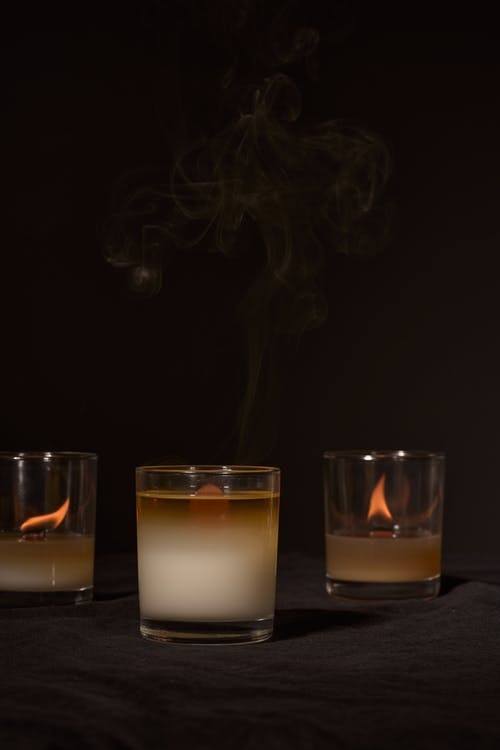 Burning aromatic candles with burning blazes placed near smoking in glass holders on black background