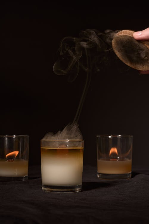Crop anonymous person extinguishing flame of aroma candle placed against black background in studio
