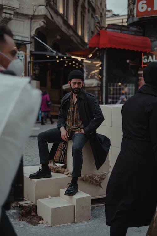 Stylish ethnic man sitting on crowded street