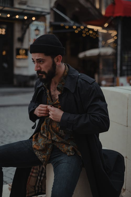 Serious ethnic male with beard buttoning up shirt while sitting on blocks on sidewalk near old fashioned residential buildings with canopies in city