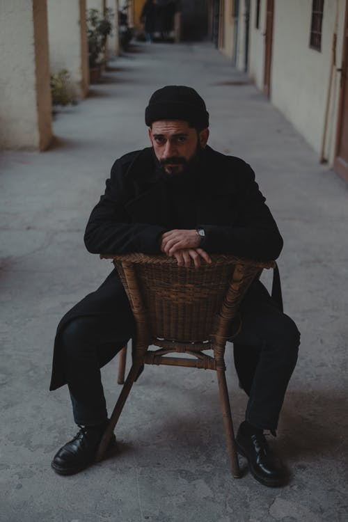 Full body male in dark outfit and cap looking at camera and sitting backwards on wooden chair in blurred corridor