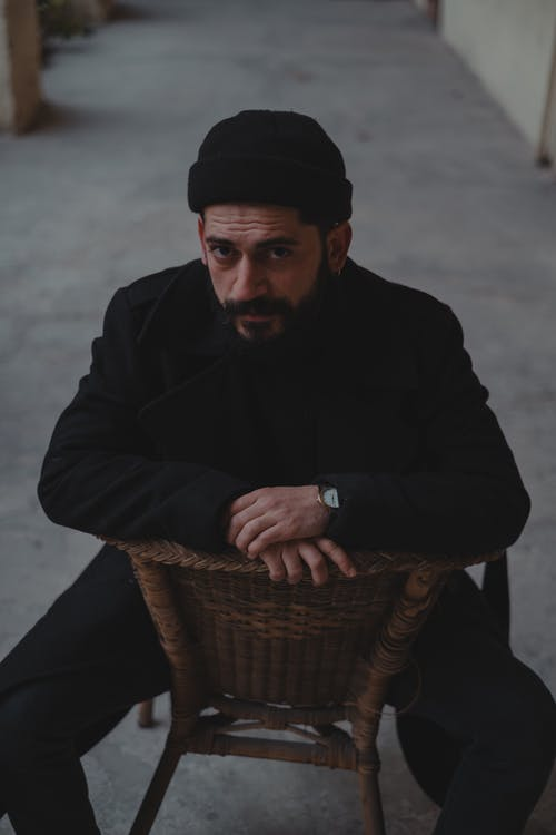 Male looking at camera while sitting backwards on wooden chair