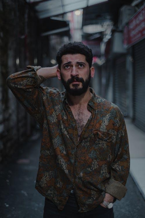 Thoughtful male standing on backstreet