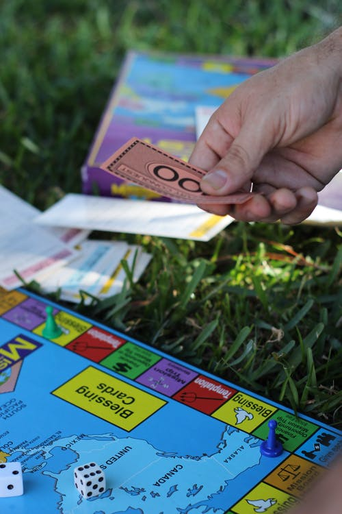 Person a Playing Monopoly Holding a Play Money