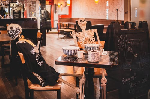 Modern cozy cafe interior with skeletons at table as decoration for Halloween holiday celebration