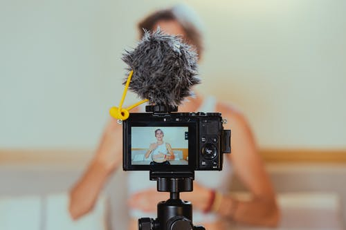 Shallow Focus Photo of a Video Camera Recording an Elderly Woman