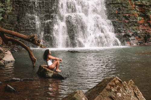 Full body side view of African American female in swimwear sitting on stone near rippling river and falling waterfall while admiring nature