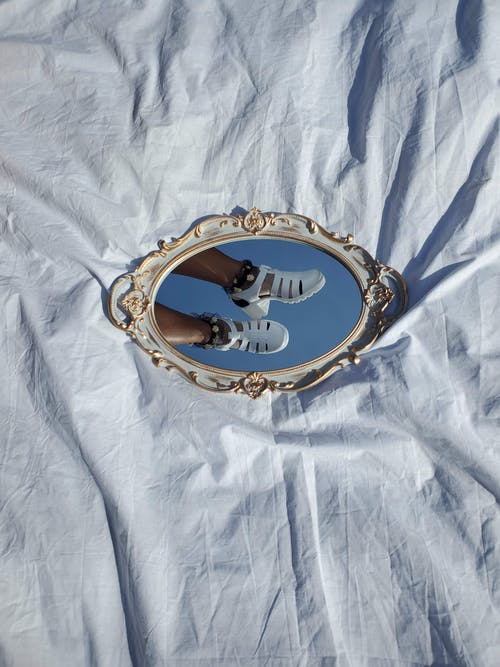 Gold and Silver Round Mirror on White Textile