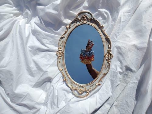 Oval Gold Framed Mirror on White Textile