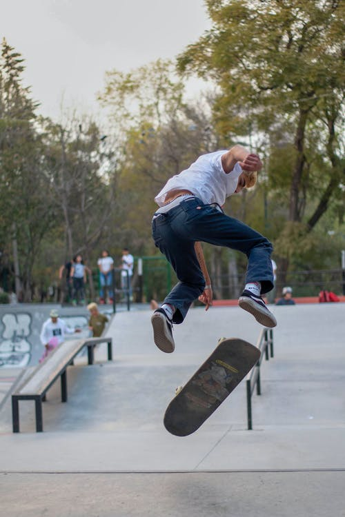 Man in White Shirt and Blue Denim Jeans Jumping on Skateboard