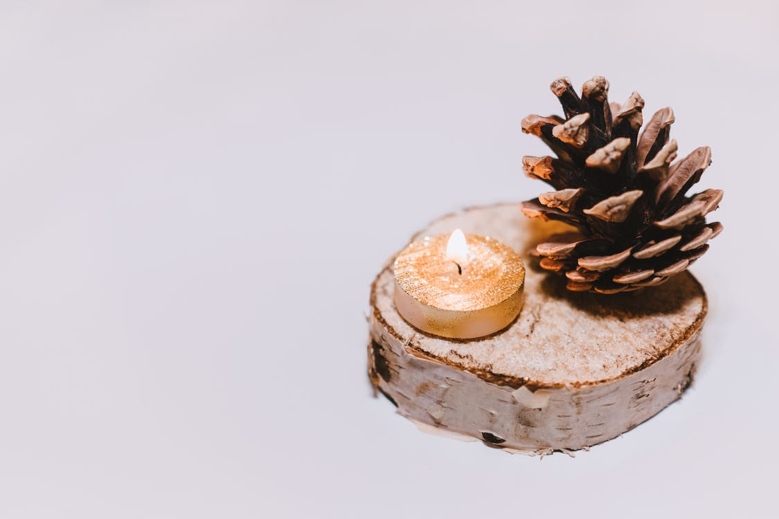 Brown Pine Cone Nut Beside Tealight Candle