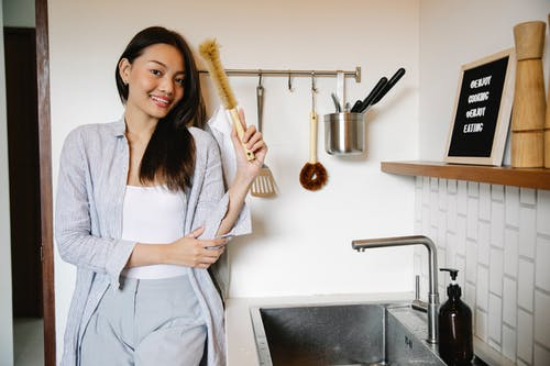 Happy Asian woman with brush for washing dishes