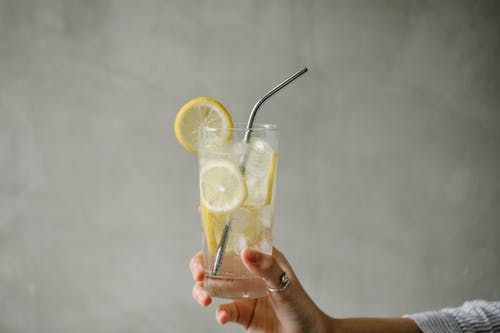 Crop woman with glass of lemonade